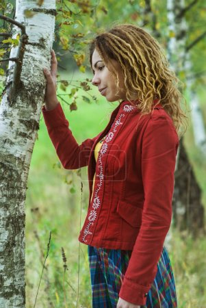 Photo for Young beautiful woman with dreadlocks in red clothes near birch. - Royalty Free Image