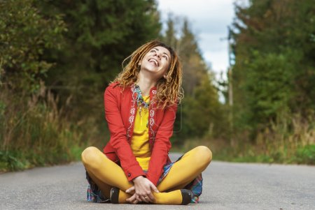 woman with dreadlocks sitting in lotus position