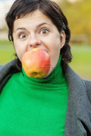 Girl bites off an apple