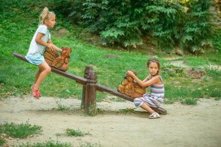 Foto de Paseo de dos hermanas en columpios contra la naturaleza verano. - Imagen libre de derechos