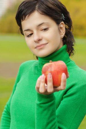 smiling cute woman bites ripe apple