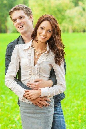 Foto de Encantadora pareja enamorada contra el parque verde de verano . - Imagen libre de derechos