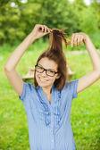 Krásná mladá dívka brýle hřebenů vlasy