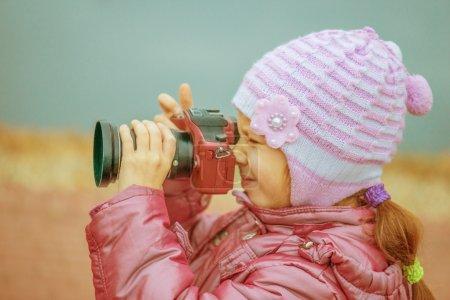 Photo pour Belle petite fille en manteau rose avec des photos de caméra rouge - image libre de droit