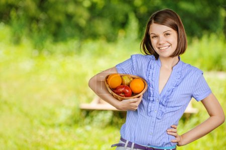 Portrait of young smiling brunette holding basket with fruits