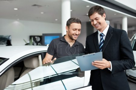 Photo for Young man with a salesman in a motor show - Royalty Free Image
