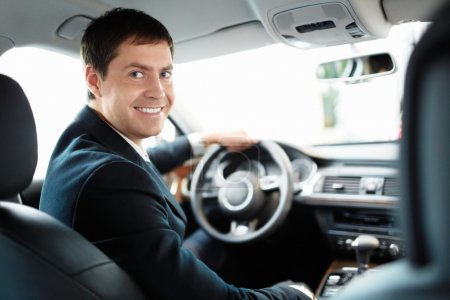 Photo for Man in a suit driving a car - Royalty Free Image