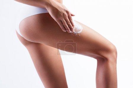 Photo pour Femme mettre la crème sur les hanches isolé - image libre de droit