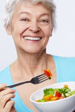Photo for Elderly woman eating salad on white background - Royalty Free Image