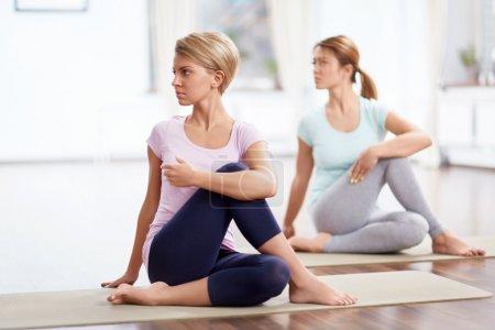 Photo pour Les jeunes filles font du yoga à l'intérieur - image libre de droit