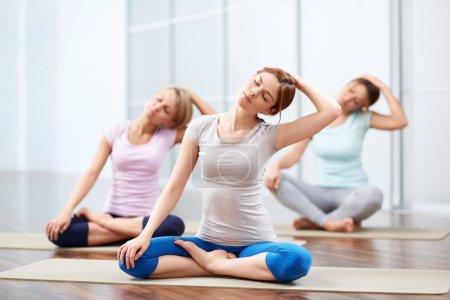 Photo pour Jeunes filles font du yoga à l'intérieur - image libre de droit