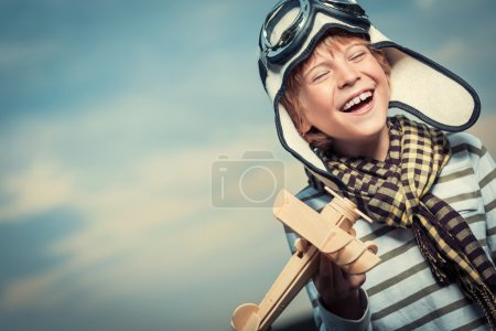 Photo for Laughing boy with plane on the background of sky - Royalty Free Image