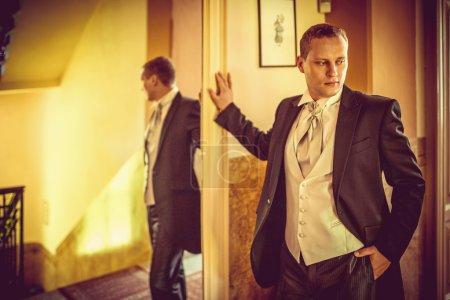 Photo pour Jeune homme en costume dans un miroir - image libre de droit