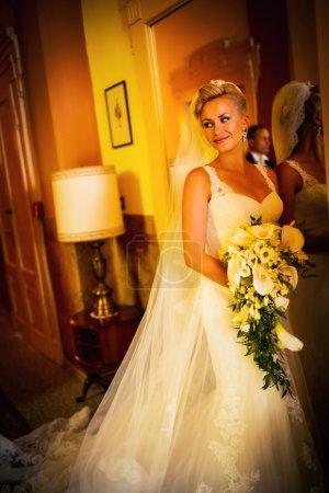 Photo pour Mariée en robe de mariée blanche à un miroir - image libre de droit