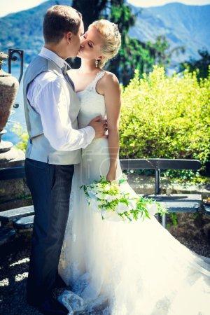 Photo pour Embrasser mariée et marié à l'extérieur - image libre de droit