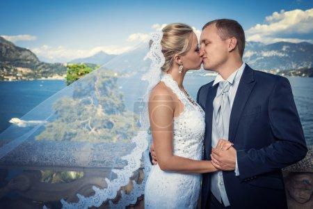 Photo pour Embrasser un couple marié dans un paysage - image libre de droit