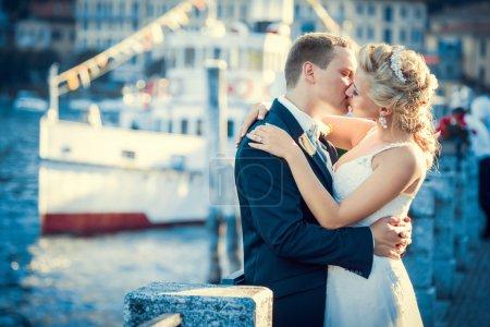 Photo pour Embrasser couple de mariage en plein air - image libre de droit
