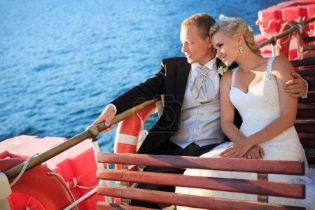 Photo pour Mariés embrassant sur un bateau - image libre de droit