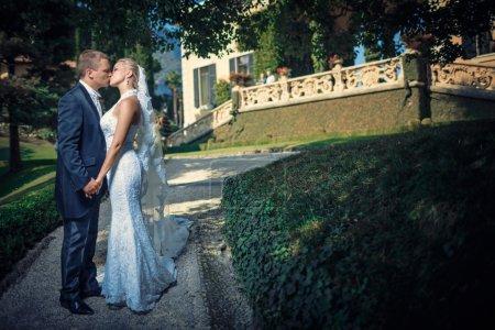 Photo pour Embrasser les jeunes mariés à l'extérieur - image libre de droit