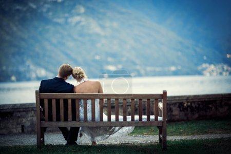 Photo pour Jeune couple nouvellement marié sur un banc - image libre de droit