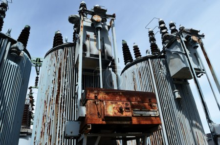 Photo for Old rusty transformer substation against the blue sky, horizontal - Royalty Free Image