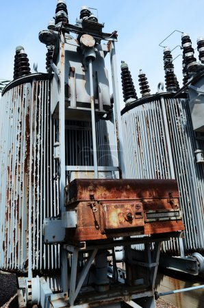 Photo for Old rusty transformer substation against the blue sky, vertical - Royalty Free Image