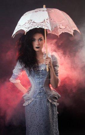 Surprised beautiful Halloween vampire woman aristocrat with lace