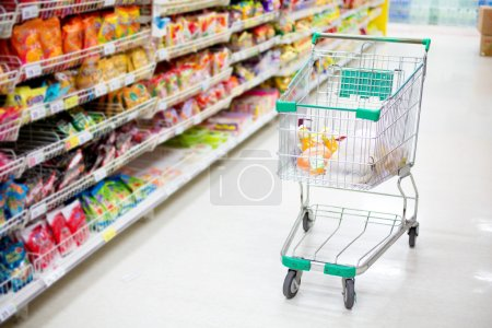 Photo for Shopping trolley in aisle of supermarket - Royalty Free Image