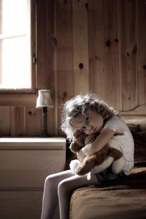 Sad little girl hugging teddy bear