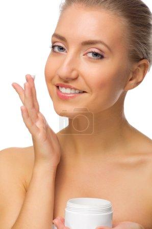 Photo pour Jeune fille appliquant crème isolée - image libre de droit