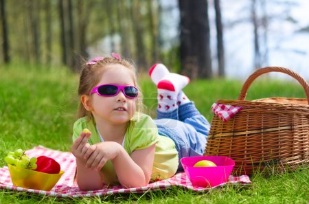 Little girl eating grapes at picnic