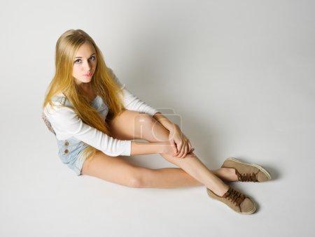 Photo pour Jeune fille assise sur le sol sur fond gris - image libre de droit