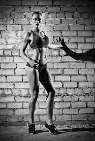 Photo for Muscular woman on grey brick wall (monochrome version) - Royalty Free Image