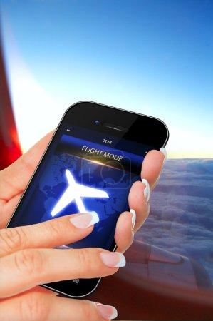Photo pour Gros plan de la main qui tient le téléphone portable avec mode de vol dans l'avion - image libre de droit