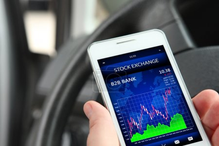 Hand holding cellphone with stock exchange screen