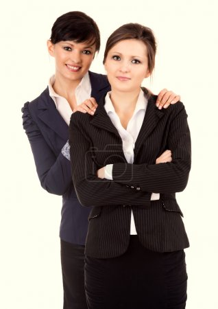 Portrait of two happy young business women standing and smiling,
