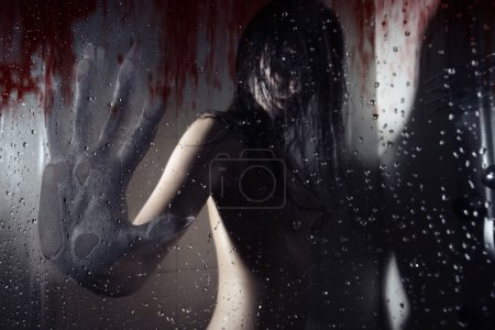 Photo for Werewolf in the dark bathroom touching wet bloody glass by his huge hand with sharp nails. Natural darkness. Artistic colors and grain added - Royalty Free Image