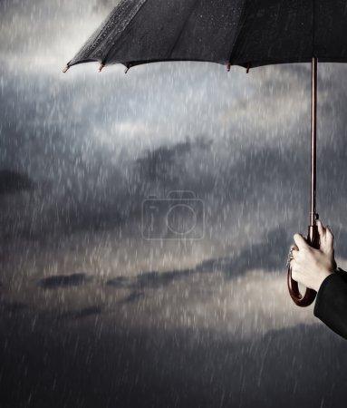 Photo pour Les mains humaines tenant grand parapluie noir sous la pluie forte - image libre de droit