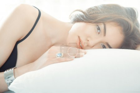 Brunette lady with jewelry laying on the bed...