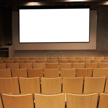 Photo pour Cinéma vide avec écran isolé blanc et marron chaises - image libre de droit