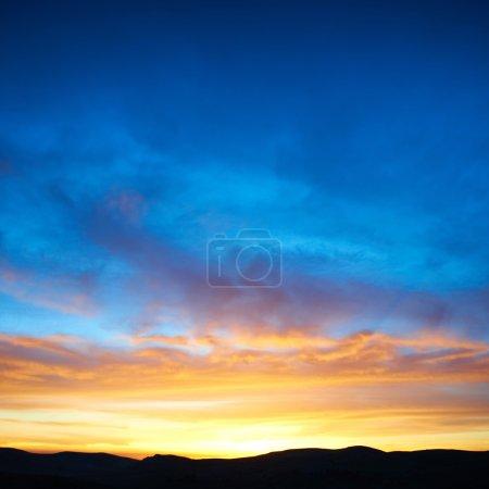 Photo pour Terre avec et ciel coloré dramatique au coucher du soleil - image libre de droit