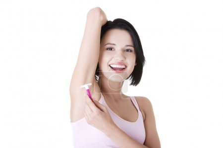 Smiling young woman shaving her armpit