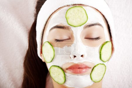 Photo for Young woman with cucumber slices on the face in a spa saloon - Royalty Free Image