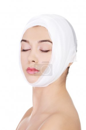 Portrait of beautiful young female face with bandage