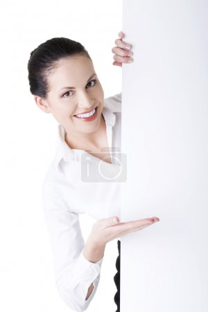 Smiling businesswoman showing blank signboard