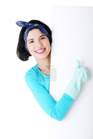 Smiling cleaning woman showing blank sign board.