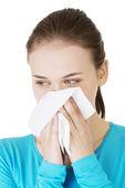 Mladá žena s tkání - kýchání. alergie nebo studené