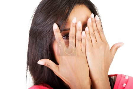 Shy woman peeking through covered face.