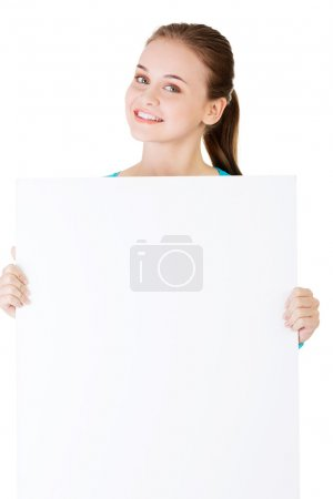 Attractive woman holding a poster with copy space.