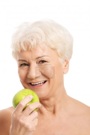 Nude old woman holding and apple.
